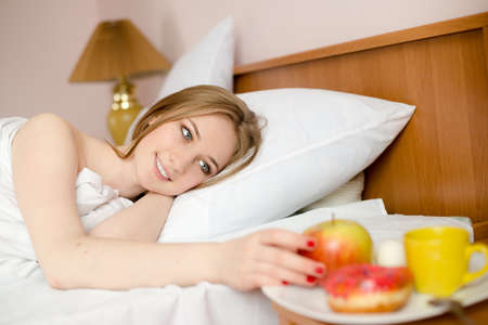 portrait of sexy blonde girl lying on white bed in lingerie and looking at plate with apple, donut & cup of hot drink on light copy space background photo