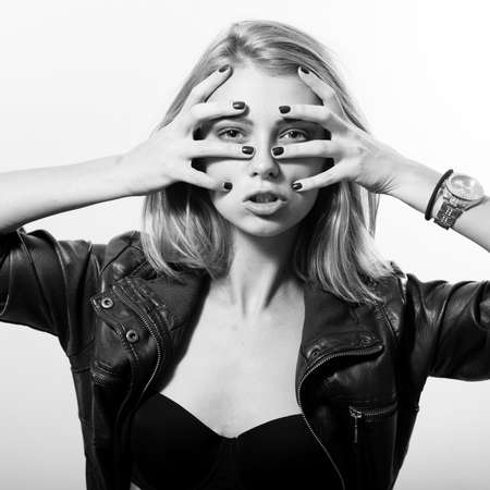 black and white portrait of sexy young blonde woman posing emotionally covering face & looking at camera over light copy space background photo