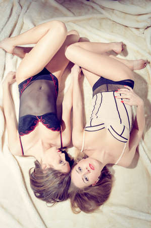 portrait on 2 sensual gorgeous sexy pinup girlfriends having fun relaxing together in bed on light copy space background photo