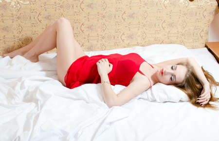 charming sleeping beauty: portrait of elegant sensual beautiful female having fun in red dress lying on the white bed with sexy legs up on copy space background Stock Photo