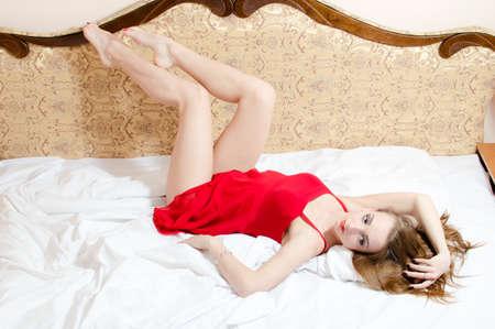 魅力的な眠れる森の美女: セクシーな足上げコピー領域の背景の白いベッドに横たわっている赤いドレスで楽しい時を過す優雅な官能的な美しい女性
