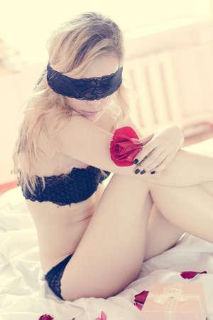 ojos vendados: retrato de los ojos vendados elegante señora bastante joven que se divierte con olor rosa de la flor. mujer romántica de la piel de seda pinup relax en la cama la luz de fondo copia espacio.