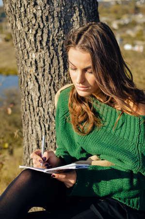 portrait of beautiful young woman having fun writing notes on sunny outdoors copy space background photo