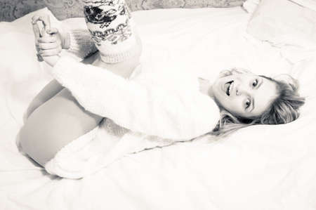 portrait of beautiful blond sexy young woman on white bed copy space background wearing just hand made jumper and knee socks, happy smiling and looking at camera photo