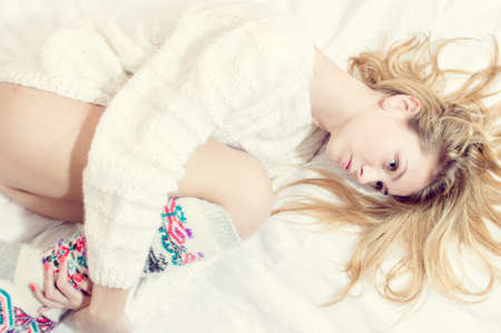 blue eyes beauty in bed: portrait of beautiful blond sexy young woman on white copy space background wearing just hand made jumper and knee socks