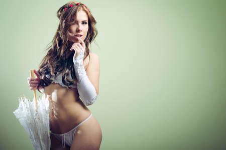 ragazza nuda: ritratto di sensuale, guardando la fotocamera bella giovane sposa in bianco lingerie con perfetta forma del corpo sexy che tiene l'ombrello del merletto sulla luce verde copia spazio sfondo