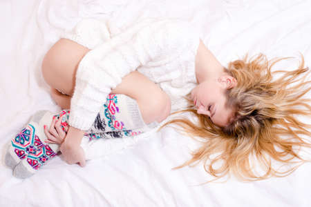 image of sleeping beautiful blond sexy young woman on white bed copy space background