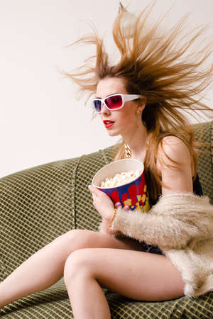 blown away: hair blown away beautiful young lady having fun watching movie in 3d glasses holding popcorn with mouth wide open & hair blown away on light copy space background