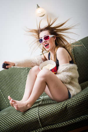 great film moments: beautiful girl having fun watching movie in 3d glasses with popcorn holding remote control with mouth wide open & hair blown away on light copy space background photo