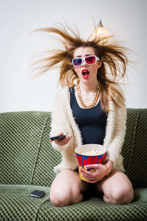great movie moments: portrait of funny blond pretty girl having fun watching tv movie in 3d glasses with popcorn holding remote control & mouth wide open on light copy space background photo