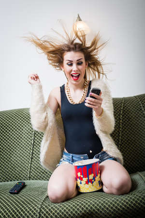 great news: portrait of funny young blond pretty woman having fun watching tv movie with popcorn and holding mobile phone, excited happy screaming on light copy space background photo