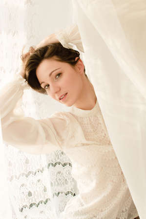 portrait of elegant beautiful young lady in white dress looking at camera on copy space tulle curtain background photo