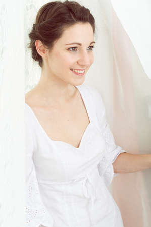 portrait of elegant beautiful young lady in white dress happy smiling on copy space tulle curtain background photo
