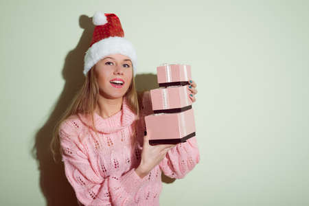 portrait of happy smiling Santa Girl in Christmas hat holding gifts boxes on light green copy space background photo