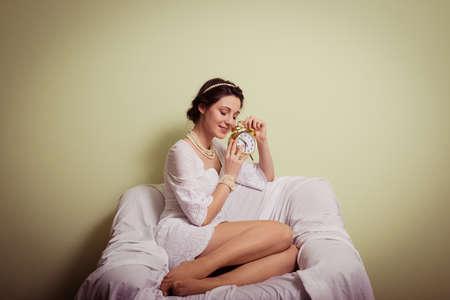 vestidos de epoca: retrato de elegante dama joven y hermosa en el vestido blanco divertirse celebraci�n taza de bebida feliz sonrisa en copia espacio de fondo