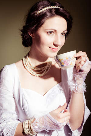 portrait of drinking tea or coffee beautiful young lady in white dress having fun happy smile on copy space background