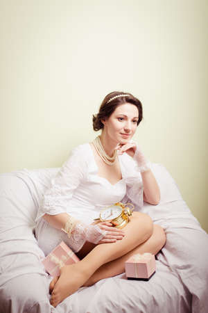 perls: portrait of elegant beautiful young lady in white dress having fun holding present boxes and golden clock happy smile on copy space background