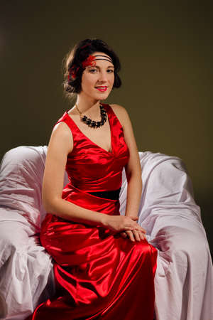 portrait of aristocracy retro styled beautiful young lady in red dress relaxing sitting in chair happy smile and looking at camera on copy space background photo