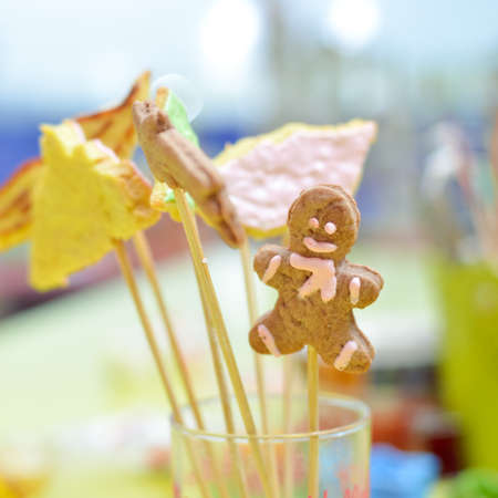 closeup on gingerbread cookies on stick in glass photo