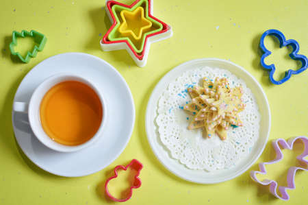 image of cookies on white plate with molds and cup of tea photo