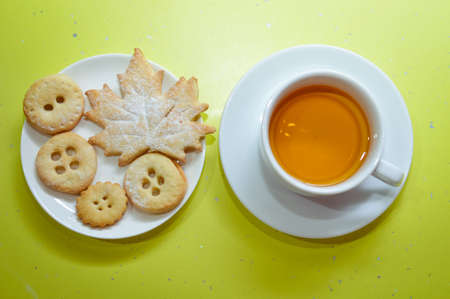 bickie: Cup of green tea and homemade festive cookies over bright green copy space background Stock Photo