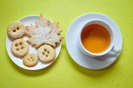 bickie: Picture of button cookies and cup of tea on green background Stock Photo