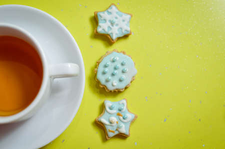 Handmade ginger cookies and cup of tea on green background photo