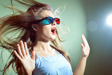 wind blown hair: Picture of surprised young pretty lady in 3d glasses looking amazed