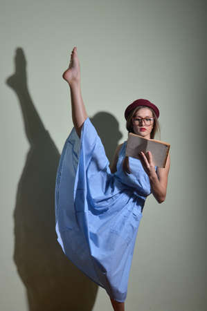 splitting up: Portrait of pretty ballet dancer in a red bowler hat and glasses reading a book Stock Photo
