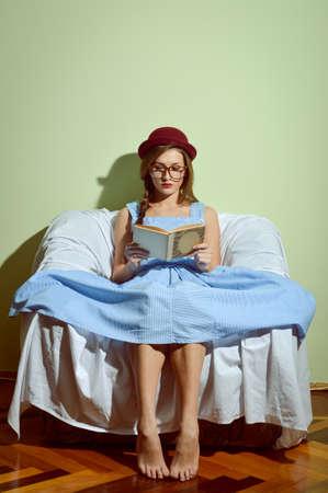 ragazze a piedi nudi: Ragazza in vetri e cappello rosso seduta sul divano a leggere un libro Archivio Fotografico