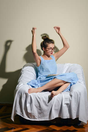 Portrait of beautiful girl in glasses sitting on the couch reading a book with hands up in dance photo