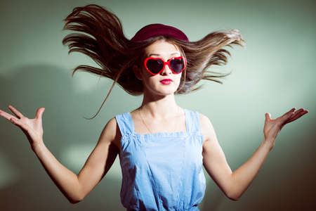 hair blown away surprised girl with glasses in the shape of hearts photo
