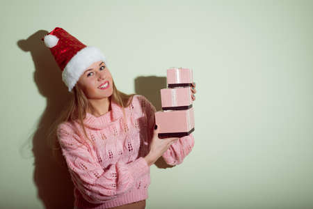 exciting pretty girl in Santa hat with gifts photo