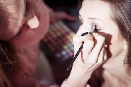 closeup on girl doing another girl makeup photo