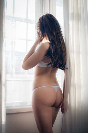 sex education: Picture of beautiful bride in white lingerie relaxing looking out the window Stock Photo