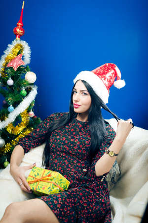 Portrait of beautiful cheerful girl with Santa hat holding gift box & happy smiling looking at camera photo