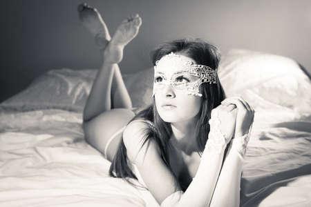 Cerca de la imagen de la hermosa joven en ropa interior se relaja en la cama, blanco y negro Foto de archivo - 38267620