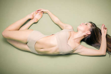 naked silhouette: Portrait of beautiful sexy young lady with perfect fit body in flying shape on gray copy space background