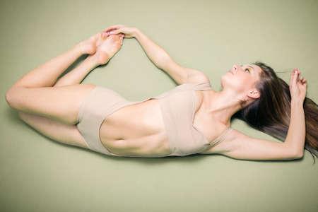 mujer sexy desnuda: Retrato de la se�ora hermosa joven atractiva con la carrocer�a perfecta en forma en forma de volar en el espacio de copia fondo gris