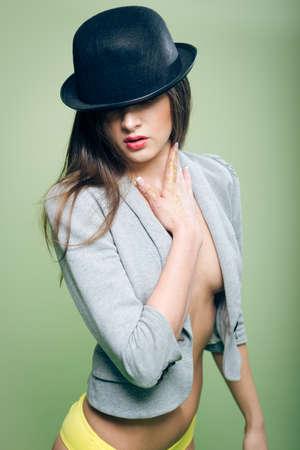 senos desnudos: Retrato de rom�ntica atractiva hermosa joven en el sombrero de bomb�n y la ropa interior de color amarillo con los pechos desnudos y el est�mago en el fondo espacio de la copia