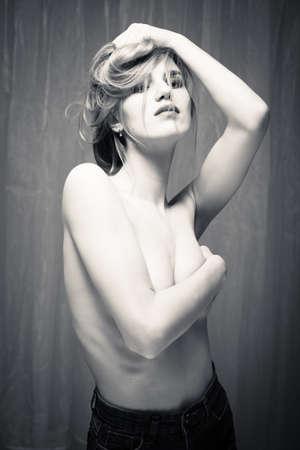 mujer sexy desnuda: Retrato blanco y negro de las tetas al aire atractiva hermosa joven en el fondo de cortina de luz