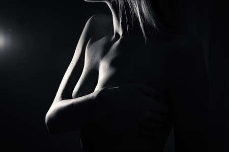 big boobs: Primer blanco y negro de las tetas al aire atractiva mujer joven hermosa en fondo oscuro Foto de archivo
