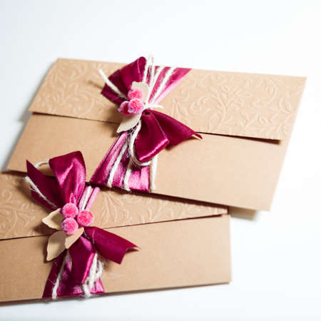 Close up on two envelopes with ribbon bow on light background photo