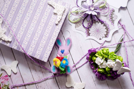 Picture of artistic handmade rabbit gift box and decorations on wooden table background photo