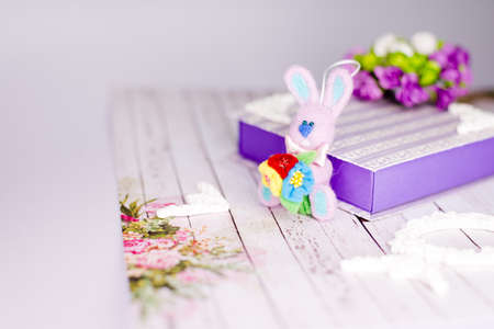 Artistic handmade rabbit, gift box and decorations on wooden table background photo