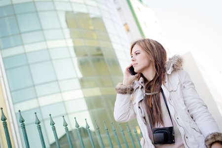 Portrait of beautiful young lady speaking on mobile phone on city glass building background photo