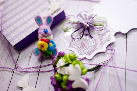 Picture of artistic handmade rabbit, gift box and decorations on wooden table background photo