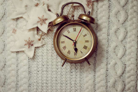 magic hour: Image of alarm clock on knitted background sorounded with decorative stars