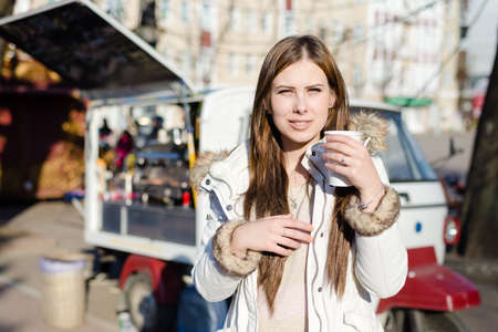 having fun in winter time: Portrait of young pretty woman with a cup of hot drink on sunny outdoors background