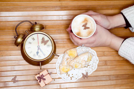 having fun in winter time: Image of hands holding cup of hot drink with pastries on plate small gift box and alarm clock around